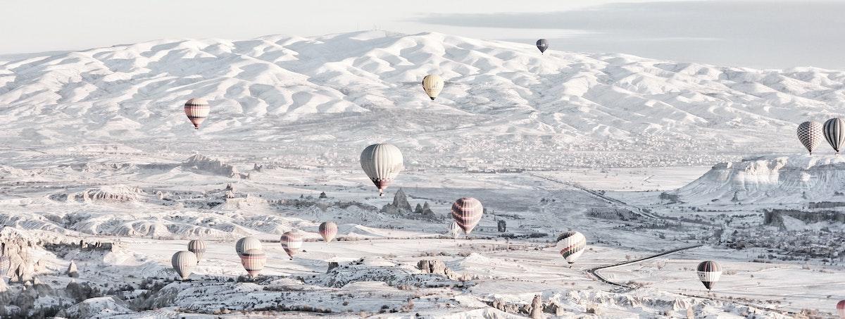 montagne enneigé avec montgolfières